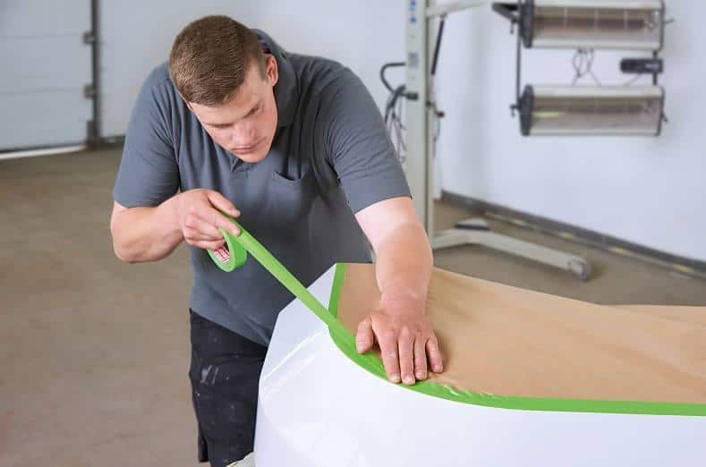 a worker applies tesa 4338 high performance masking tape to a surface in order to mask it off for a spray-painting coat. The tape quick to stick thanks to its high initial tack and bond strength.