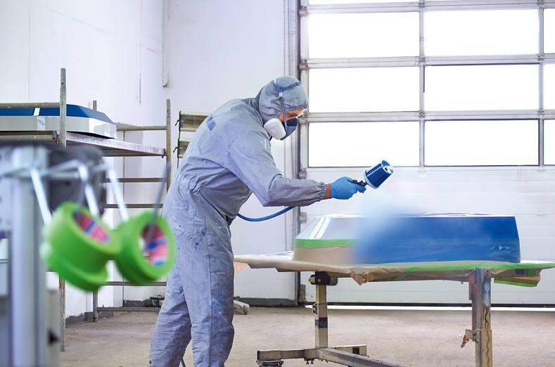 a worker spray-painting a surface while tesa 4338 high performance masking tape protects the rest of the surface.